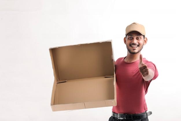 Gelukkig aziatische man in t-shirt en pet met lege doos geïsoleerd op witte achtergrond, levering dienstverleningsconcept