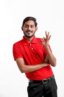 Gelukkig aziatische man in t-shirt en pet staande op een witte achtergrond, levering dienstverleningsconcept