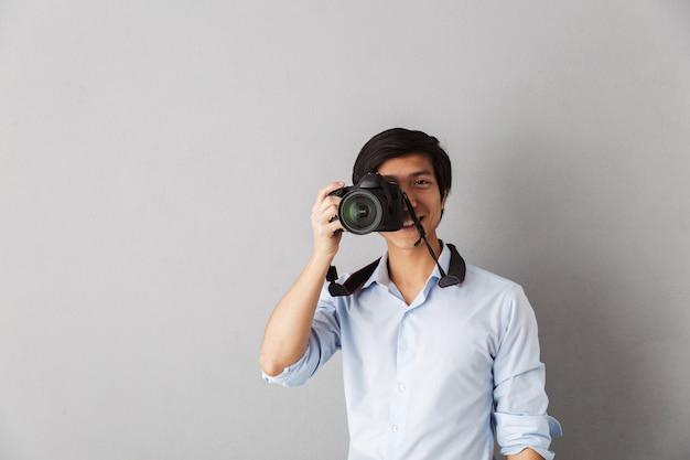 Gelukkig aziatische man permanent geïsoleerd, een foto nemen met fotocamera
