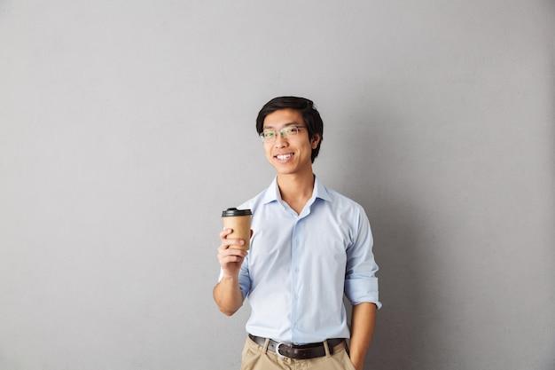 Gelukkig aziatische man permanent geïsoleerd, kopje afhaalmaaltijden koffie te houden