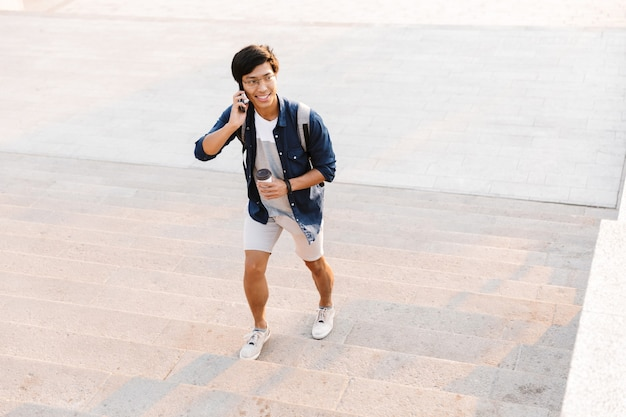 Gelukkig aziatische man praten op mobiele telefoon tijdens het wandelen naar boven buiten met kopje koffie