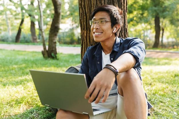 Gelukkig aziatische mannelijke student in bril met laptop wegkijken zittend in de buurt van de boom in het park