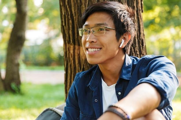 Gelukkig aziatische mannelijke student in bril wegkijken zittend in de buurt van de boom in het park
