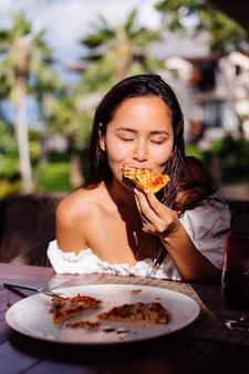 Gelukkig aziatische mooie vrouw hongerig met pizza op zonnige dag zonsondergang licht in openluchtrestaurant vrouw genieten van eten met plezier tijdens de lunch