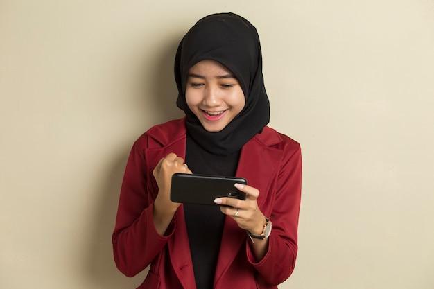 Gelukkig aziatische moslimvrouw opgewonden om spelletjes te spelen op haar slimme telefoon