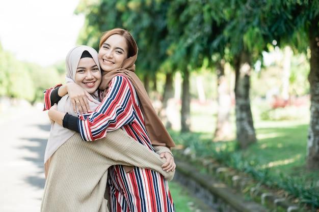Gelukkig aziatische moslimvrouwen in hijaabs buiten op zonnige dag met vriend omarmen