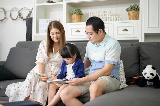 Gelukkig aziatische ouder onderwijs kleine schattige dochter huiswerk en tekening samen thuis.