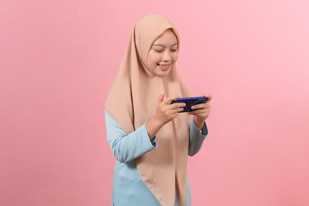 Gelukkig aziatische portret mooie schattige jonge vrouw tiener glimlachend tekstbericht typen op slimme mobiele telefoon geniet van online communicatie geïsoleerd op roze achtergrond