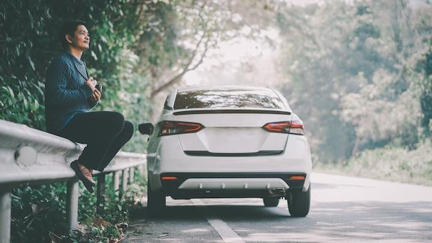 Gelukkig aziatische reiziger man op de weg met witte auto en camera vast te houden.