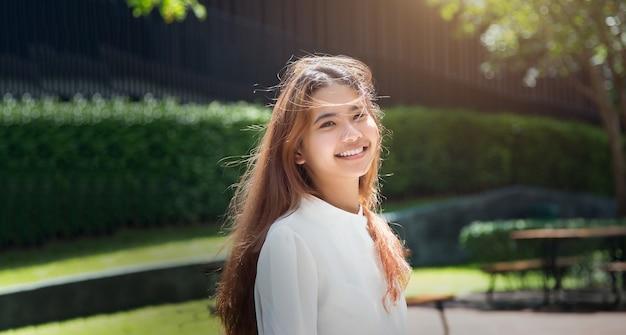 Gelukkig aziatische tiener vrouw glimlach naar camera buiten park in zonnige dag