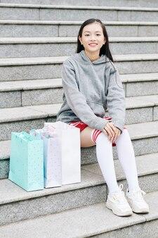 Gelukkig aziatische tienermeisje zittend op stappen naast papieren zakken na het winkelen in winkelcentrum