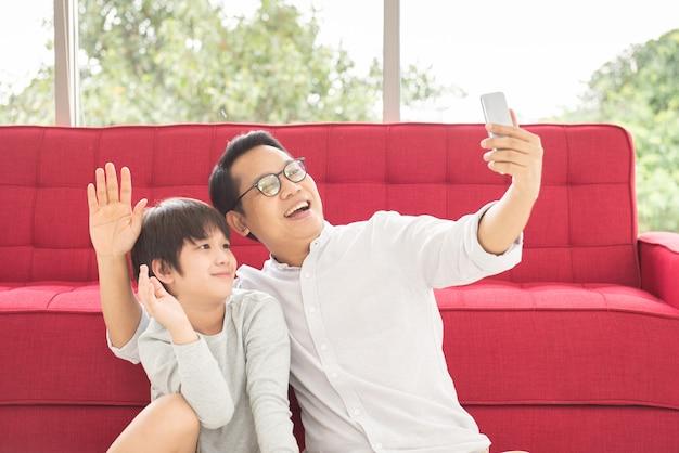 Gelukkig aziatische vader en zoon met videochat op slimme telefoon zittend op de vloer terug leunende rode bank.