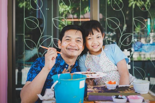 Gelukkig aziatische vaderdag. grappige lachende vader en haar dochter schilderen en tekenen met waterverf