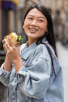 Gelukkig aziatische vrouw buiten een hamburger eten