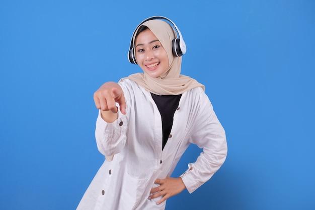 Gelukkig aziatische vrouw die lacht luisteren naar muziek in de koptelefoon