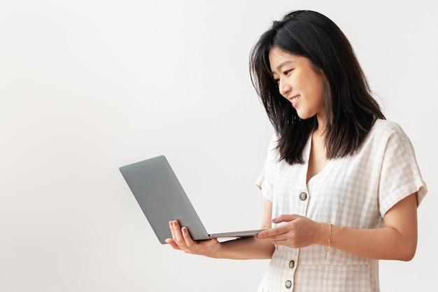 Gelukkig aziatische vrouw die vanuit huis werkt