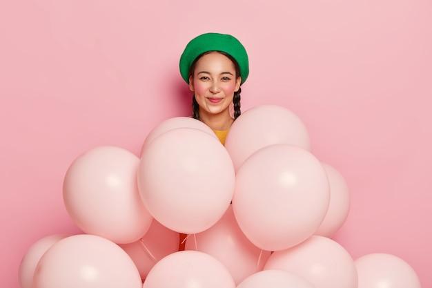 Gelukkig aziatische vrouw draagt groene trendy baret, komt op vrolijk feestje, staat achter heliumballonnen