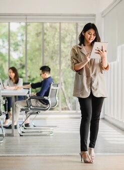 Gelukkig aziatische vrouw met behulp van digitale tablet met collega