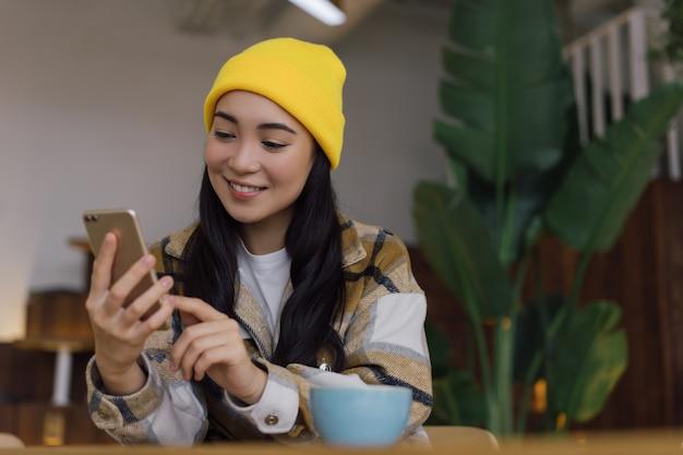 Gelukkig aziatische vrouw met behulp van mobiele telefoon, communicatie, online winkelen, om thuis te zitten