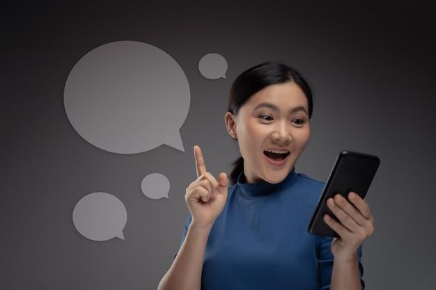 Gelukkig aziatische vrouw met behulp van slimme telefoon en pictogram hologrameffect