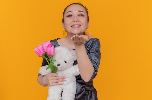 Gelukkig aziatische vrouw met boeket roze tulpen en teddybeer blaast een kus