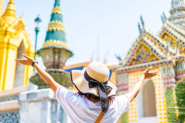 Gelukkig aziatische vrouw reizen bij tempel in thailand
