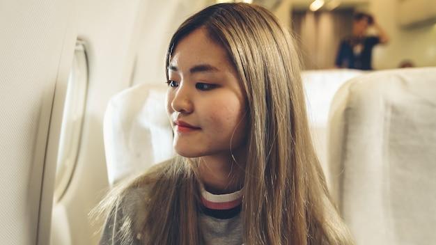 Gelukkig aziatische vrouw reizen in vliegtuig