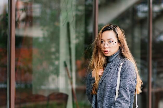 Gelukkig aziatische vrouw student op de straat in de stad