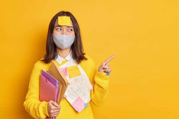 Gelukkig aziatische vrouwelijke manager bezig met papierwerk draagt beschermend wegwerpmasker tijdens coronavirus pandemie geeft wijsvinger op kopie ruimte