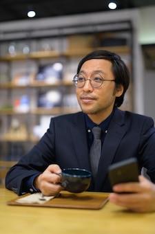 Gelukkig aziatische zakenman denken terwijl koffiekopje en ph