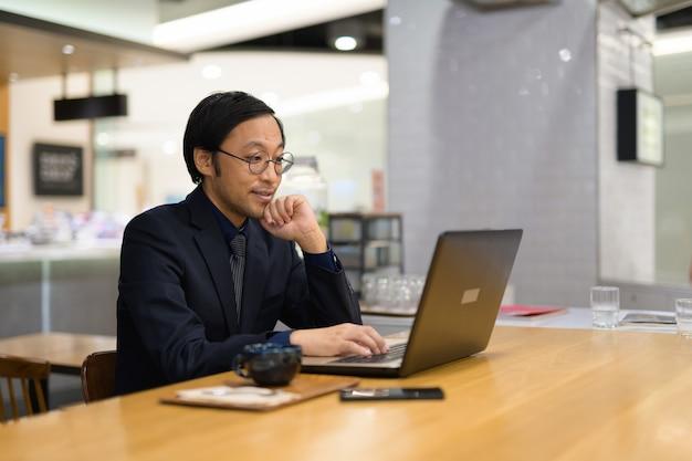 Gelukkig aziatische zakenman denken tijdens het werken bij de koffiesho