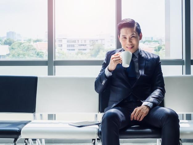 Gelukkig aziatische zakenman in pak witte kop warme koffie drinken zittend op stoel wachten in de buurt van groot glazen raam met zonlicht