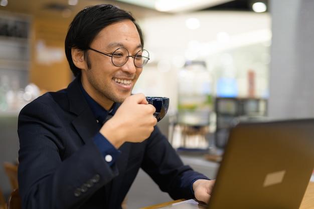 Gelukkig aziatische zakenman koffie drinken tijdens het werken bij koffie