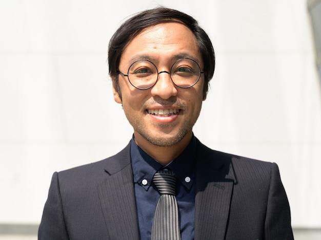 Gelukkig aziatische zakenman lachend op betonnen muur