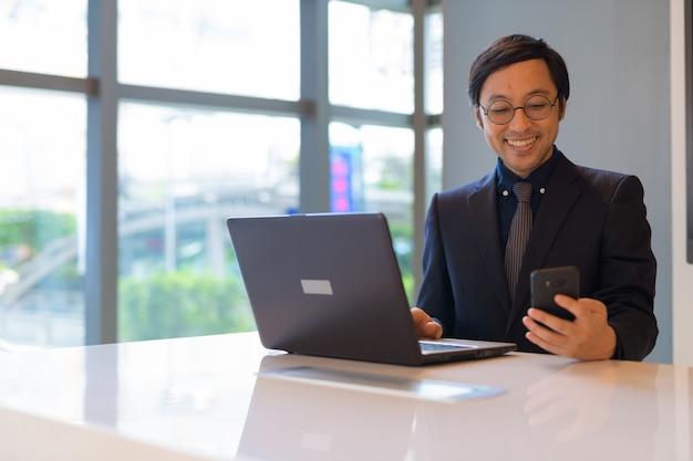 Gelukkig aziatische zakenman met laptop en telefoon bij het raam