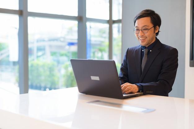 Gelukkig aziatische zakenman met laptop op kantoor bij het raam