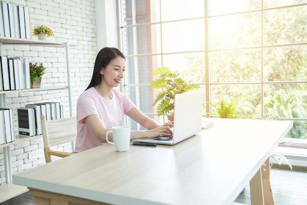 Gelukkig aziatische zakenvrouw in casual werken met laptop en glimlach op moderne kantoor of co-working space.