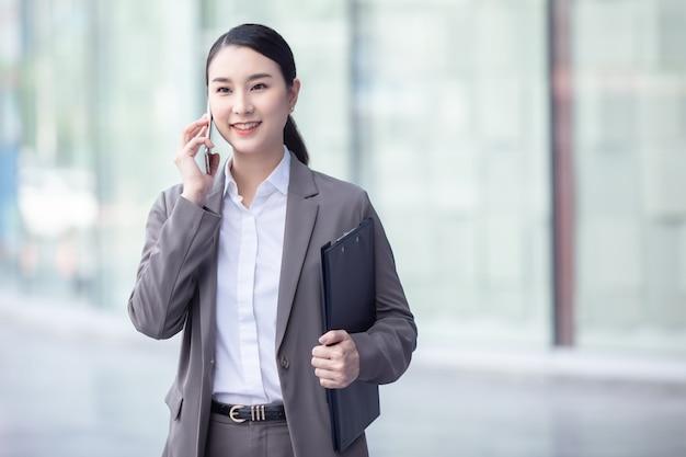 Gelukkig aziatische zakenvrouw praten via de mobiele telefoon