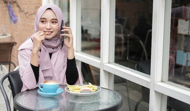 Gelukkig azië hijab vrouw met behulp van slimme telefoon en bellen, koffie drinken zittend in café