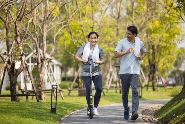 Gelukkig azië senior paar joggen buiten in park.