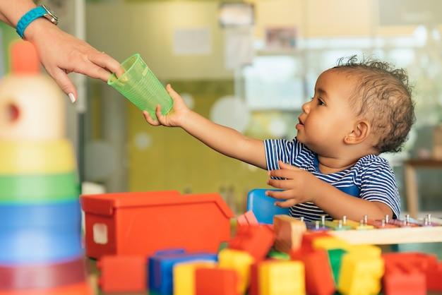 Gelukkig baby drinkwater en spelen met blokken in de kleuterschool.