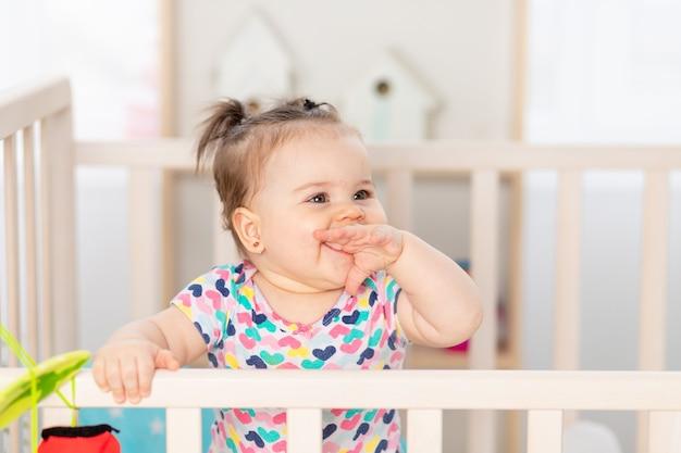 Gelukkig baby lachen thuis in de kinderkamer, portret van de baby in de wieg