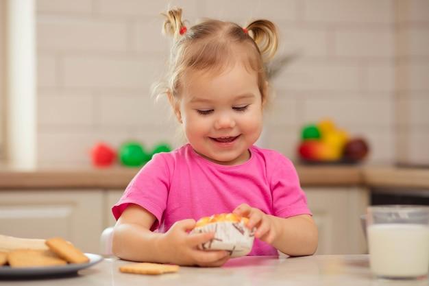 Gelukkig baby zitten aan de tafel in de keuken en eten met eetlust