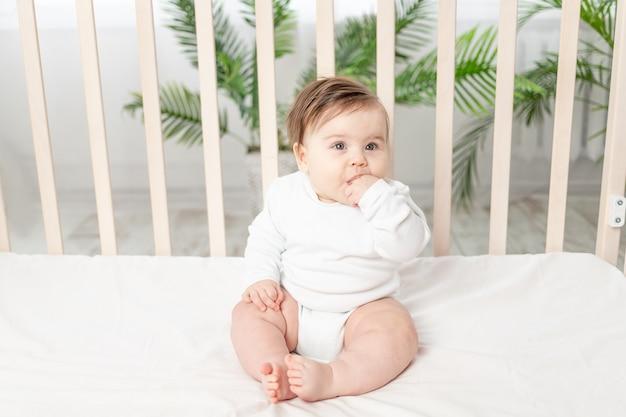 Gelukkig baby zitten in de wieg in een witte romper en zijn vinger zuigen Premium Foto