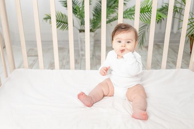 Gelukkig baby zitten in de wieg in een witte romper en zijn vinger zuigen