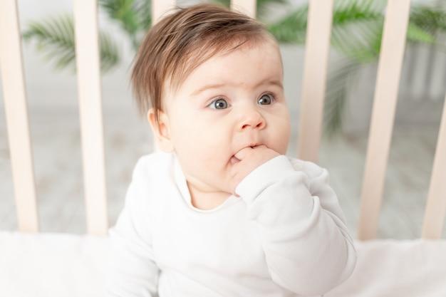 Gelukkig baby zittend in de wieg in een witte romper en zijn vinger zuigen