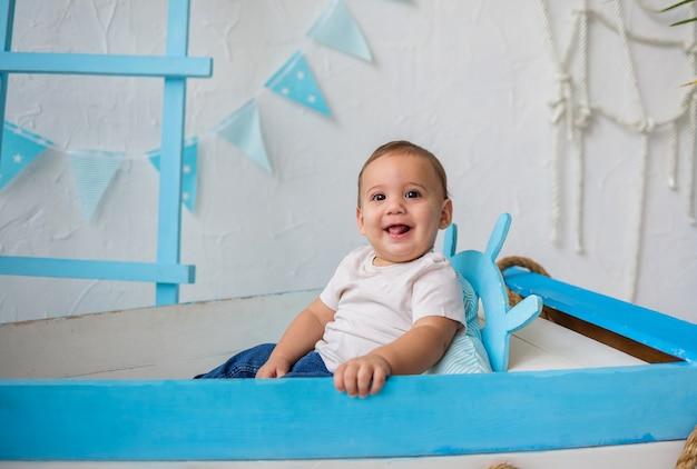 Gelukkig babyjongen en zit in een houten boot
