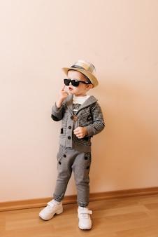 Gelukkig babyjongen in grijs pak, hoed en bril op lichte muur