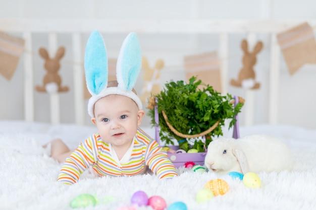 Gelukkig babyjongen met konijnenoren op zijn hoofd liggend met een konijn op het bed met paaseieren, leuke grappige glimlachende kleine baby.
