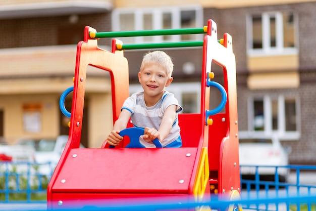 Gelukkig babyjongen spelen op de speelplaats in de tuin in de zomer